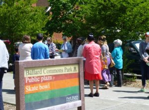 Entry sign to Ballard Commons Park, people gthering